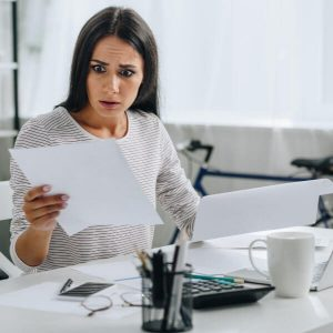 woman looking at paper with a shocked expression on her face
