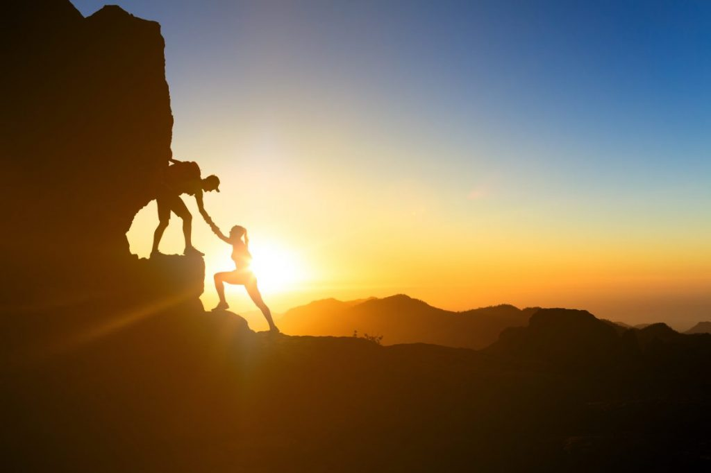 silhouette of two people rockclimbing at sunset