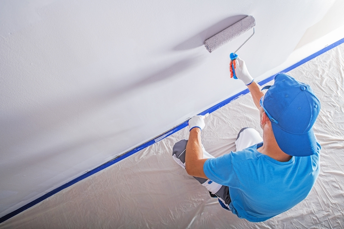 photo of man painting drywall from above