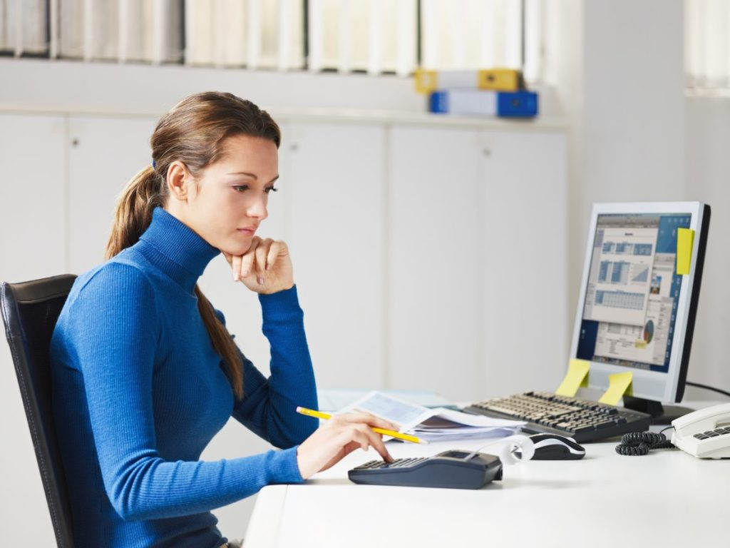 woman in blue turtleneck working on a desk