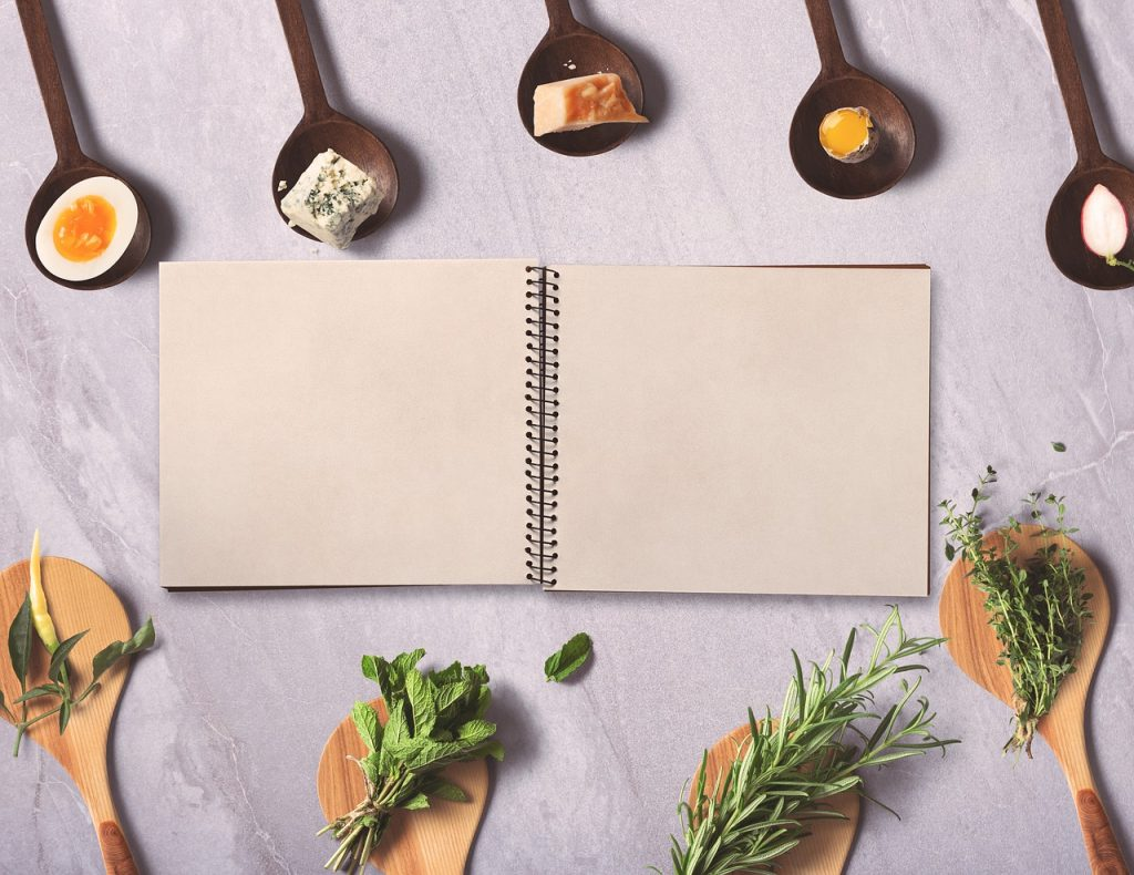cookbook type book open to blank page with ingredients around it