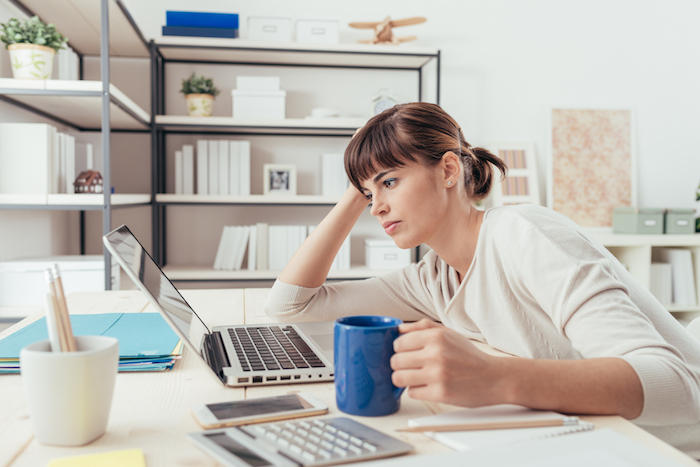 unhappy or tired woman looking at laptop while holding blue mug