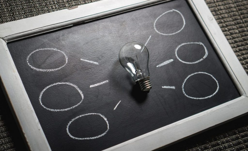 lightbulb laying on chalkboard with mind map like circles around it